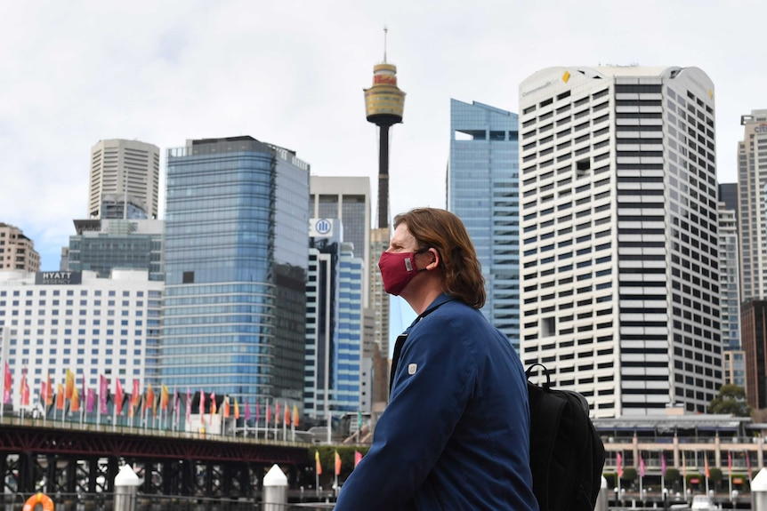a woman wearng a red mask with the sydney centrepoint tower in the background