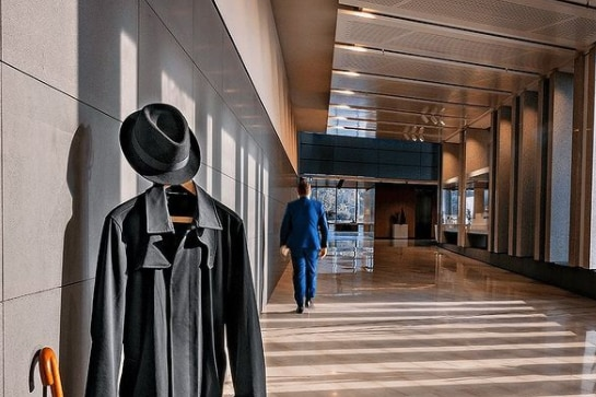 An Instagram post shows a trenchcoat on a hanger and someone walking away in normal clothes.