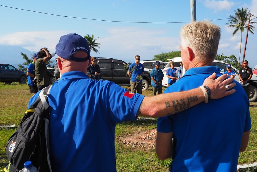 Two men in the same blue shirts stand side by side during a ceremony, one has his hand on the others back
