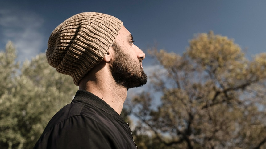 Head shot of Zohab Zee Khan looking at blue sky illustrating one of our 7 easy steps to start meditating.