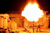 Two United States soldiers block their ears as they fire a mortar round at night in Afghanistan
