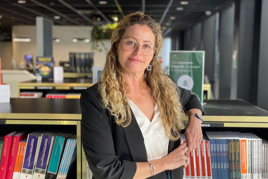 Tania Wolf in a library looking at the camera.