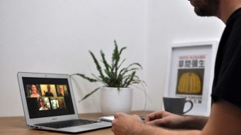 A man sits at a table participating in a Zoom meeting. On the laptop in front of him are five faces of people in the meeting.