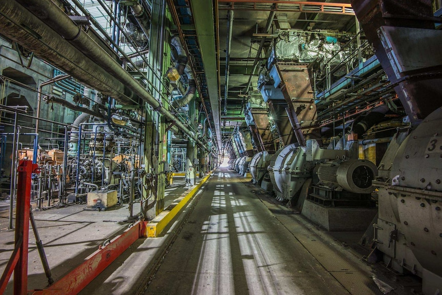 The inside of a coal power plant with coal pulverisers and other machinery lining the walls.
