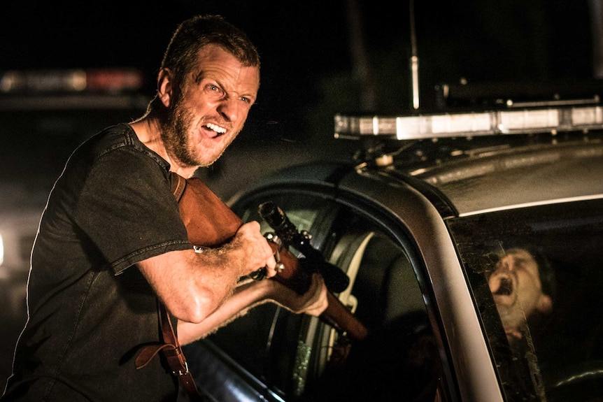 A man points a gun at the driver of a car in a still image from Killing Ground