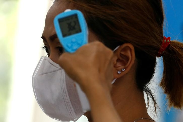 A woman wearing a facemask gets her temperature tested.