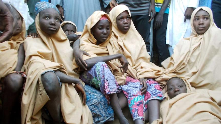 A group of Nigerian schoolgirls sit on the floor.