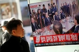 A man watches a TV broadcasting a news report on a high-level talks between the two Koreas.