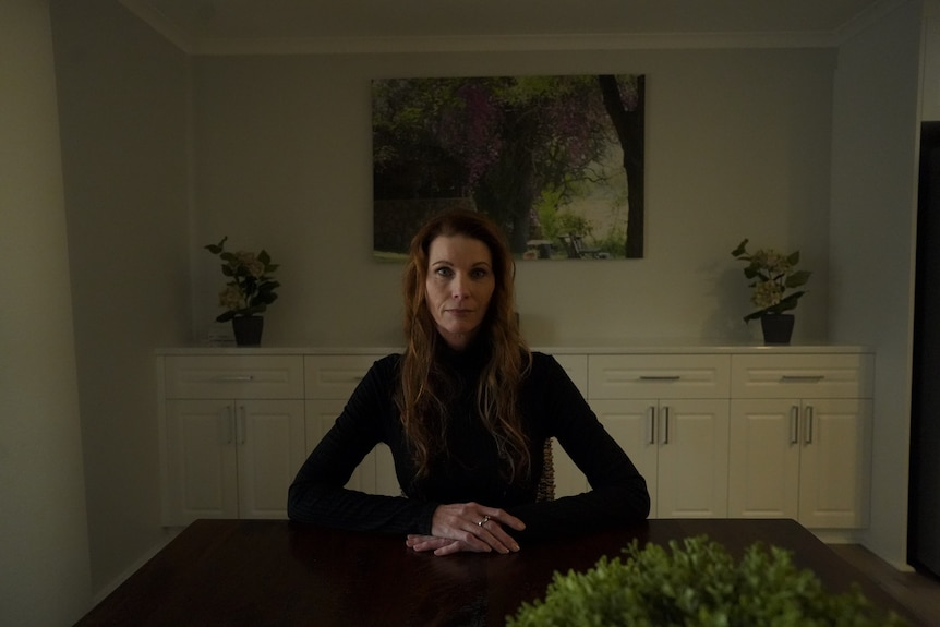 A woman in black sits at a table looking serious.
