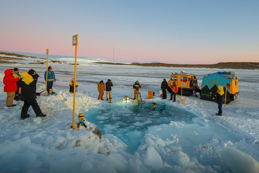 Antarctic expeditioners gather around a waterhole cut out of sea ice