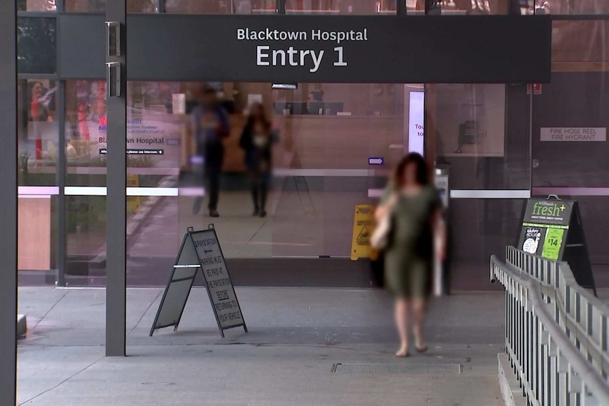 A view of the front glass sliding doors of Blacktown Hospital, people walking through