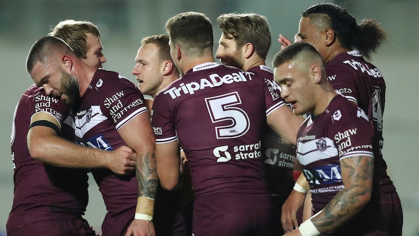 NRL players walk back to halfway after a try, quietly celebrating and patting each other on back.