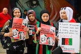 A photo of four women holding posters that say 'Save the Children of Afghanistan'.