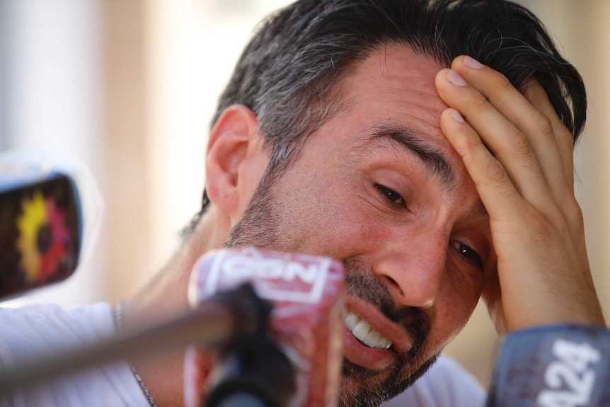 Leopoldo Luque holds his head in his hand while leaning forward in front of some journalists' microphone