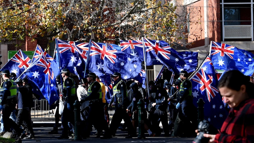 Right wing protesters from the UPF and the True Blue Crew march to Carlton Gardens with Australian flags.