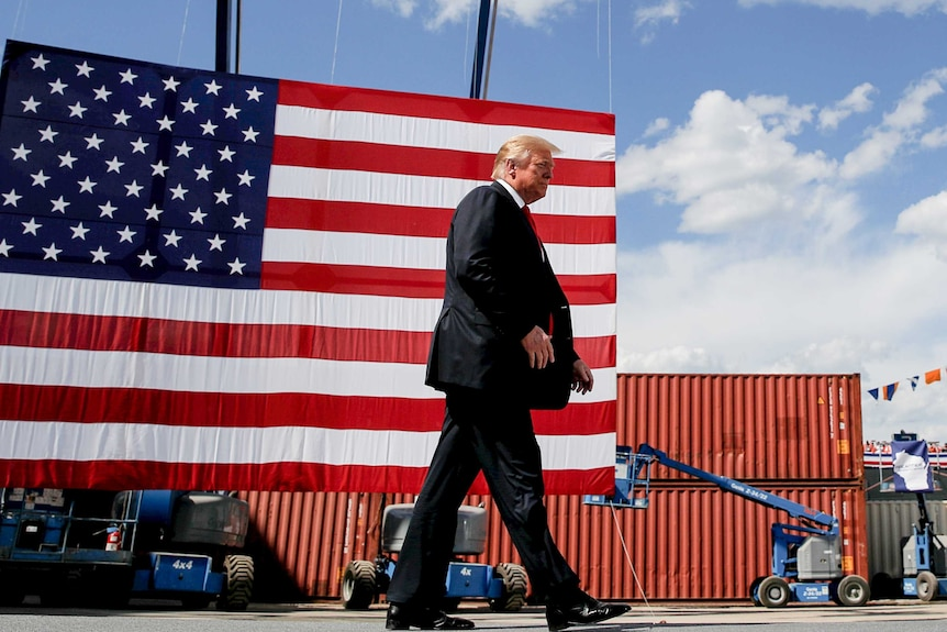 Donald Trump in a suit and red tie walking past an American flag