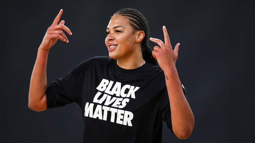 Liz Cambage smiles and holds up her hands in a black lives matter shirt.