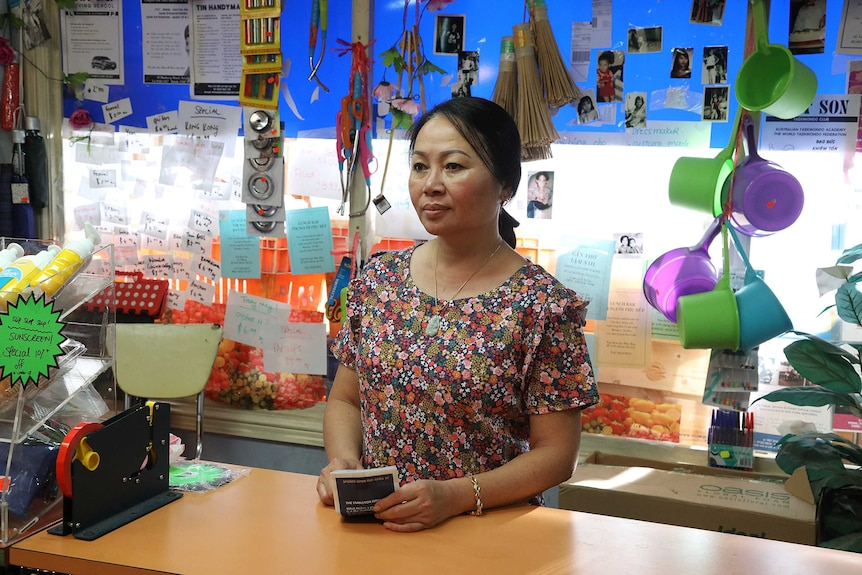 Carina Hoang as her character Iris, she is standing behind the counter of her shop, she's wearing a floral dress.