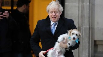 British Prime Minister Boris Johnson wears a suit and carries his dog in his arms.