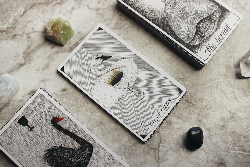 Tarot cards on a marble surface with a green and clear crystal.