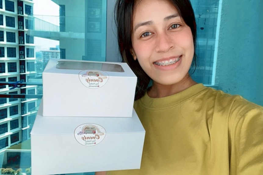 A girl with braces holding up two boxes of cookies.