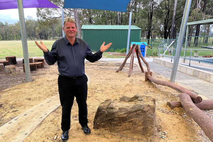 An older man stands in a primary school playground
