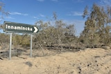 A green road sign surrounded by trees and sand.  The sign says Innamincka on it.