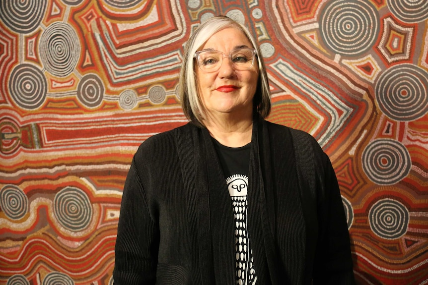 Margo, wearing lipstick, smiles in front of an Indigenous painting which is red and brown in colour.