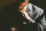 Man adjusts tie on his suit