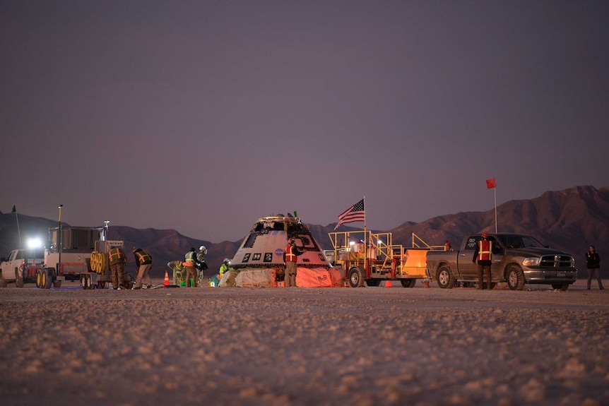 Boeing personnel work around the Boeing Starliner spacecraft shortly after it landed in the desert.