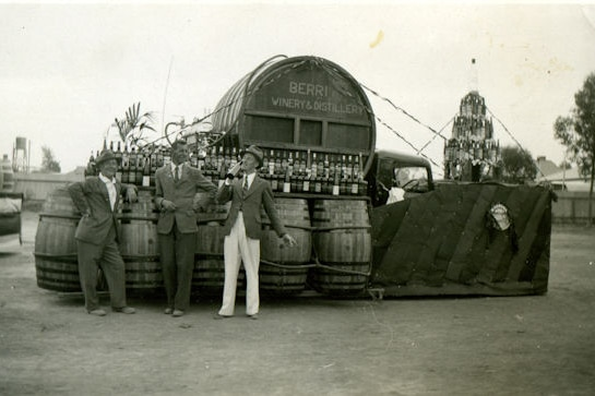 Three men are drinking wine at a bar made of wine barrels. The photo is black and white.