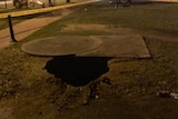 A large sinkhole in the ground near a pathway.