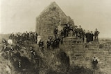 Black and white image of people posing at ruins of a brick structure.