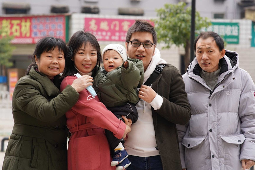 A family of five taking photos and smile happily