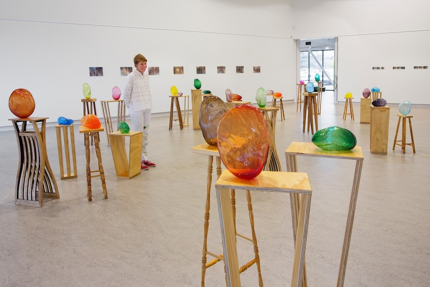Different 'hugs' sit on plinths placed around a large exhibition space, Catherine standing among them.
