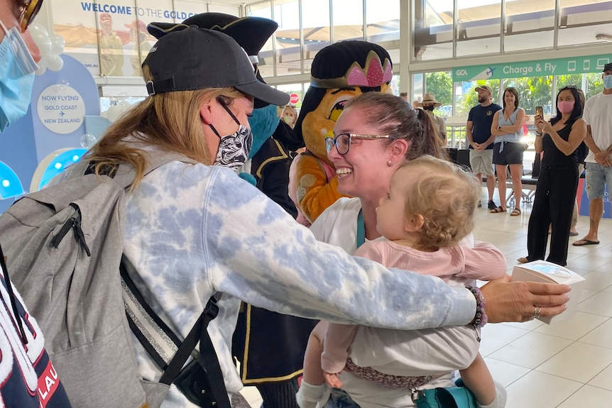 Malina Moore hugs with her sister Arna Milan who is holding her child Lucy at the airport.