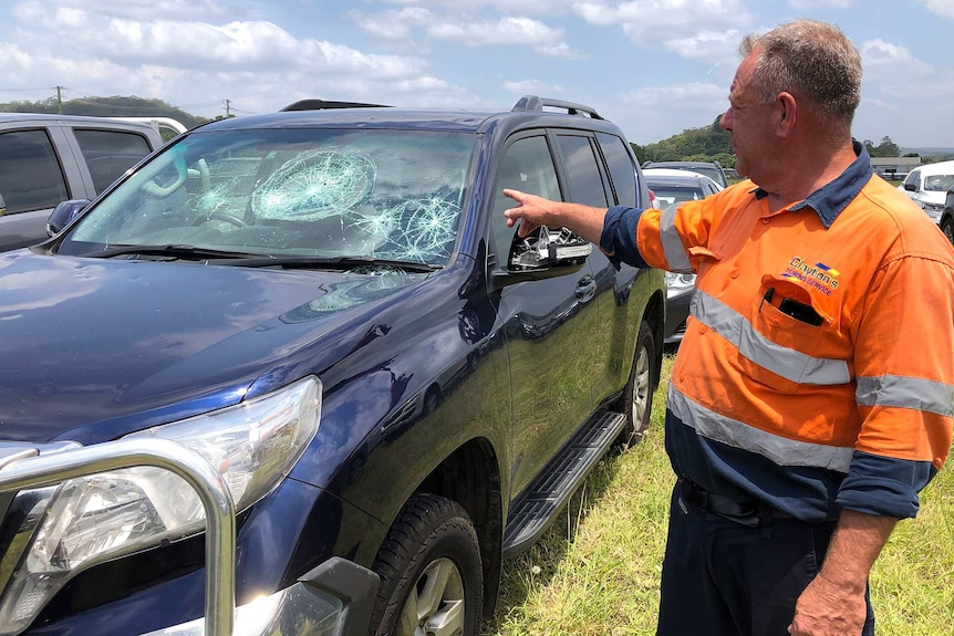 A man points at a four-wheel-drive with a hail damaged windscreen and dents.