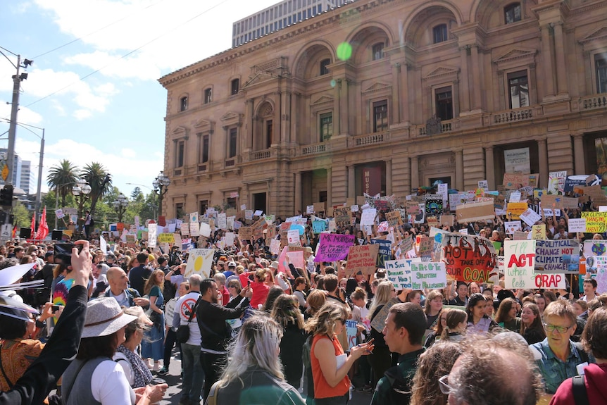 A crowd of thousands of student protesters with Victorian Parliament House in the background.