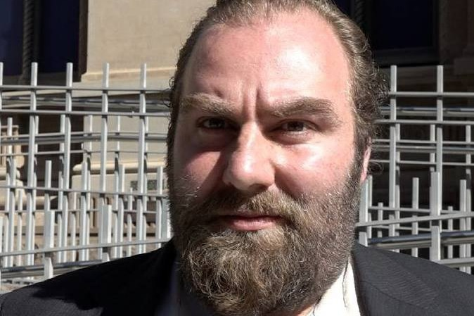 A close-up photo of Phillip Michael Galea, who has a brown beard, outside a court building.