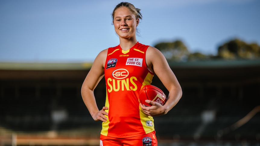 A Gold Coast Suns AFLW recruit stands with the ball held in her left hand.