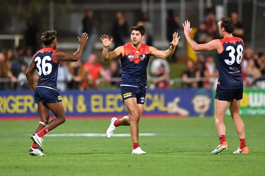 A Melbourne Demons AFL player runs as he high fives two of his teammates against St Kilda in Alice Springs.