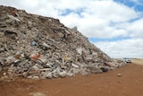 A large pile of pieces of concrete next to a four-wheel drive