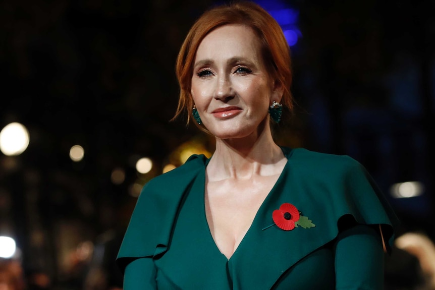JK Rowling with red hair and a poppy on her green blouse.