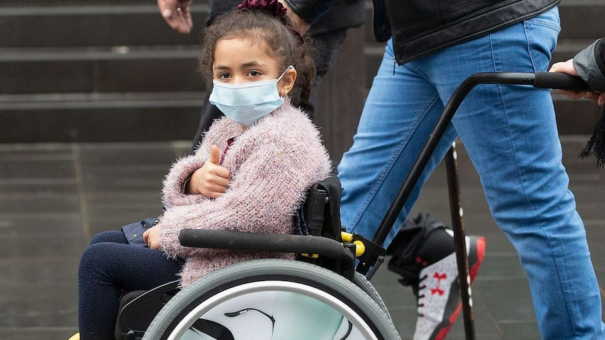 A young girl in a wheelchair wearing a mask and winter clothes gives a thumbs up as she's pushed.