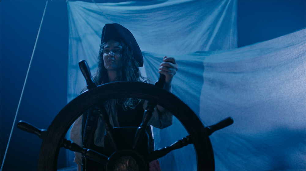 A woman with long dark curly hair wears black pirate holds steering wheel of colonial boat on a dark blue-hued night.