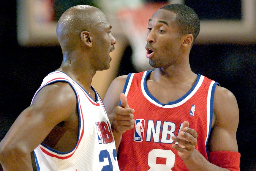 Michael Jordan in a white basketball jersey talks to Kobe Bryant in a red jersey
