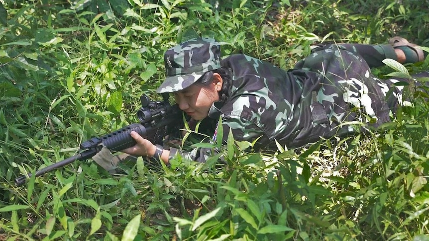 A woman wearing army fatigues lays on the ground in the grass while pointing a gun.