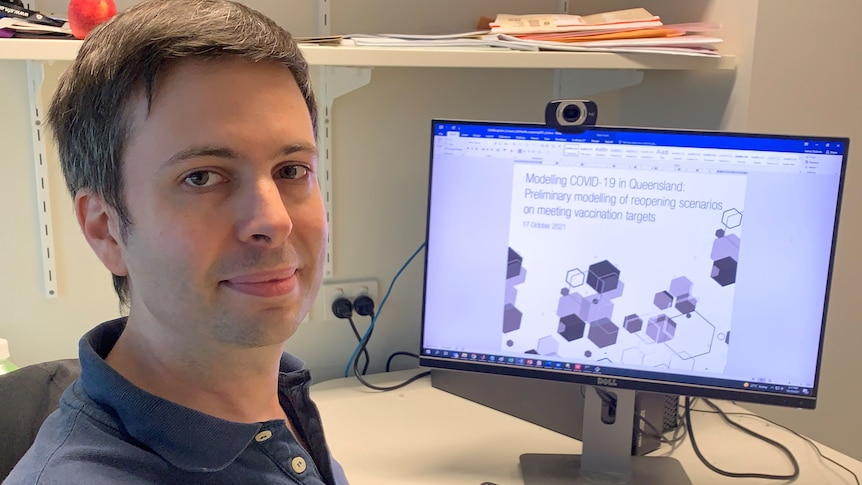 QIMR researcher James Roberts sits in front of a computer at a desk.