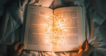 Open book on a bedspread, with hands. On the book a tangle of lights. Book is illuminated