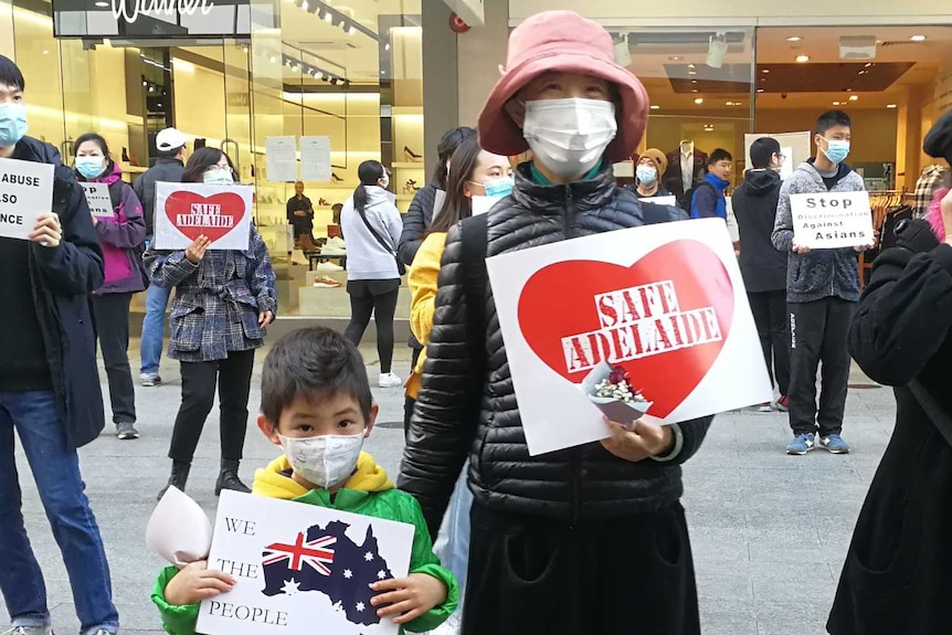 Protesters, wearing face masks, stand around 1.5 metres apart holding signs against racism in Adelaide's CBD.